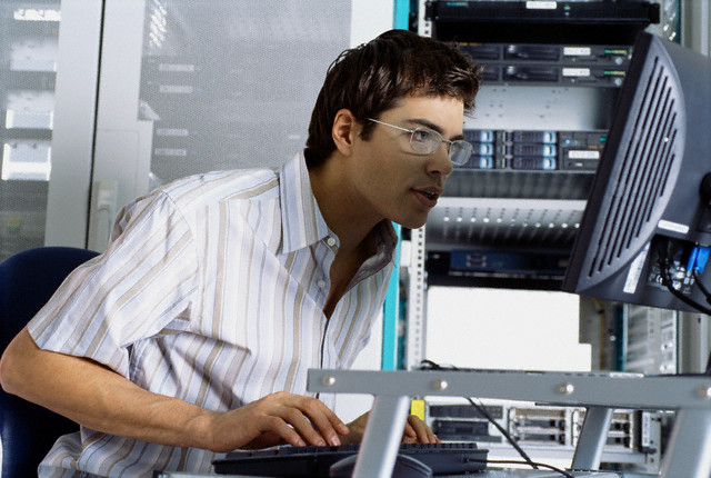 IT Worker Using Computer in Server Room --- Image by © Corbis