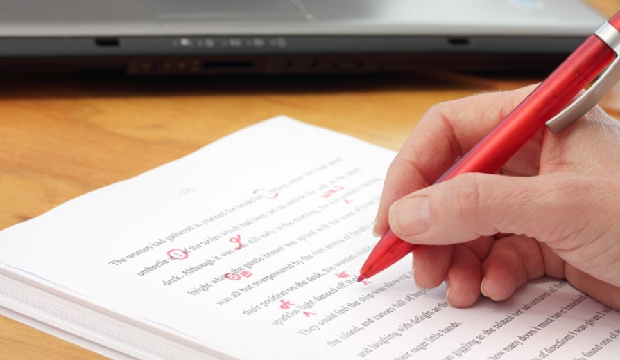 Hand with red pen proofreading by laptop