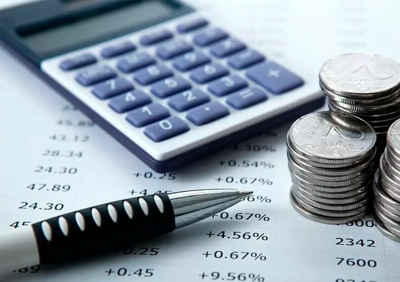 Калькулятор, ручка и мелочь на фоне документа