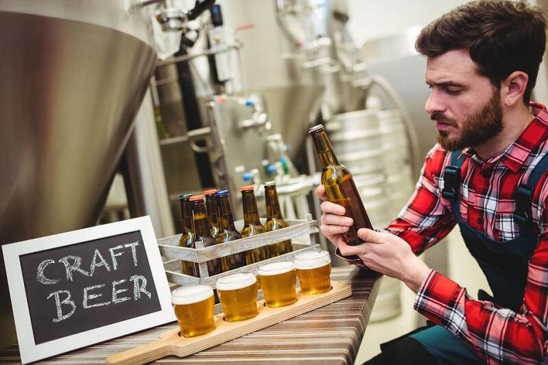 Мужчина на пивоварне держит бутылку пива в руках