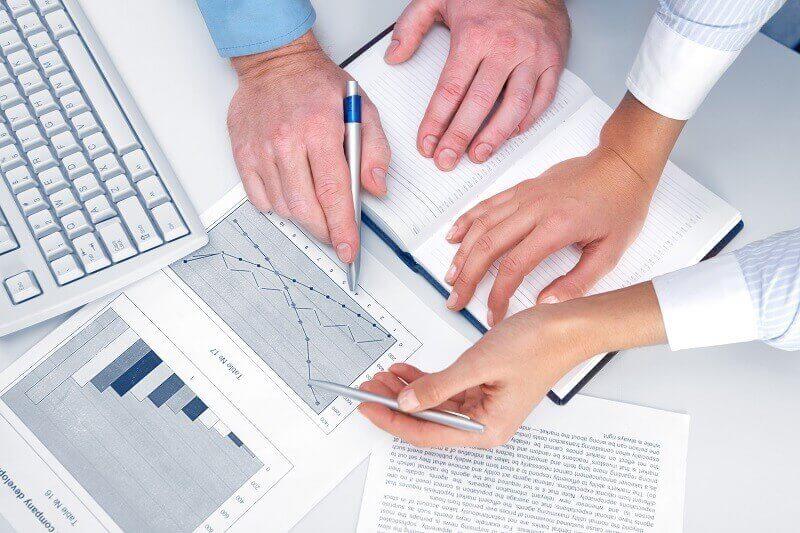 Руки мужчин с ручками составляют план