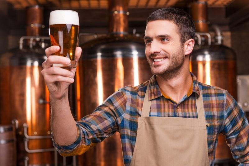 Сотрудник пивоварни с бокалом пива в руке