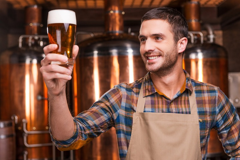 sotrudnik pivovarni s bokalom piva v ruke - Бизнес-план мини пивоварни: 7 шагов к открытию пивного бизнеса